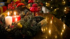 Closeup image of decorative wreath, lantern and burning candles on wooden table against glowing Christmas lights Stock Images