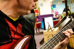 Closeup of photo of electric bass guitar player stock images