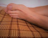 Photo of female feet on bamboo mat. Closeup photo of female feet with clear toenails polish lying on bamboo mat royalty free stock photo