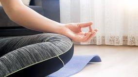 Closeup photo of female hand meditating on floor at home. Closeup image of female hand meditating on floor at home Stock Photo