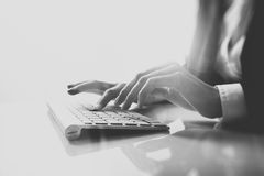 Closeup photo of female hands typing text on a wireless keyboard. Business woman working at the office. Visual effects Stock Photo