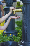 Closeup photo of girl hands push a city fountain Stock Photography