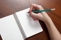 Closeup photo of girl writing in notebook with pencil. Close-up of a female hand writing on an blank notebook with a pen Royalty Free Stock Images