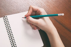 Closeup photo of girl writing in notebook with pencil. Close-up of a female hand writing on an blank notebook with a pen Royalty Free Stock Photo