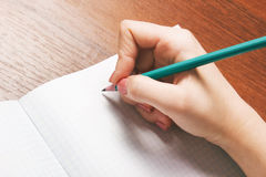 Closeup photo of girl writing in notebook with pencil. Close-up of a female hand writing on an blank notebook with a pen Stock Images