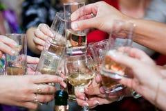 Closeup photo of hands clinking shot glasses at Royalty Free Stock Photography