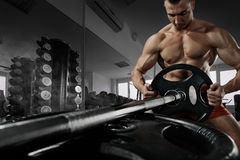 Closeup photo of handsome bodybuilder guy prepare to do exercises with barbell in a gym, keep barbell plate in hands royalty free stock photo