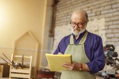 Closeup photo of handsome old craftsman writing something in the notepad. While working indoors Royalty Free Stock Images