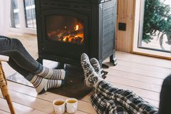 Closeup photo of human feet in warm woolen socks over fire place. Cold fall or winter day. People drinking tea and resting by the stove. Closeup photo of human royalty free stock image