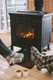 Closeup photo of human feet in warm woolen socks over fire place. Cold fall or winter day. People drinking tea and resting by the stove. Closeup photo of human stock image