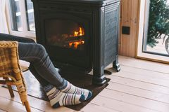 Closeup photo of human feet in warm woolen socks over fire place. Cold fall or winter day. Woman resting by the stove. Closeup photo of human feet in warm woolen stock photography