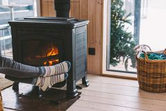 Closeup photo of human feet in warm woolen socks over fire place. Cold fall or winter day. Woman resting by the stove. Closeup photo of human feet in warm woolen stock photos