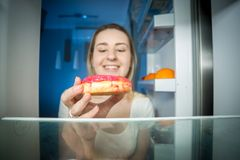 Closeup image of hungry young woman taking high-caloric donut from refrigerator at night. Concept of unhealthy nutrition. Closeup photo of hungry young woman stock photography