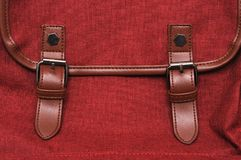 A closeup photo of the leather buckle straps of a red maroon colored bag. A photo taken on the leather buckle secure straps of a red maroon colored bag Royalty Free Stock Photo