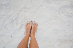 Closeup Photo Legs Young Girl Relaxing Sand Beach.Highly Detailed Image Background.Horizontal picture. Royalty Free Stock Photo