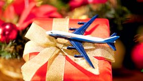 Closeup image of little airplane on Christmas gift box. Concept of winter holidays travelling. Closeup photo of little airplane on Christmas gift box. Concept of stock image
