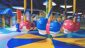 Closeup photo of little colorful carousel for small children covered with saoft mats for kids safety on the playground. Closeup image of little colorful carousel royalty free stock photography