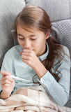 Closeup photo of little sick girl lying in bed taking digital thermometer. Royalty Free Stock Photos