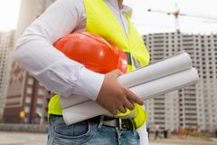 Closeup image of male engineer holding blueprints of new house and red hardhat stock image
