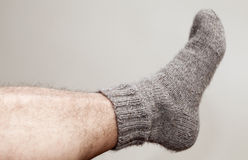 Closeup photo of male foot with woolen sock Royalty Free Stock Images
