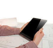 Closeup photo of man holding tablet on table with blueprints Stock Photography
