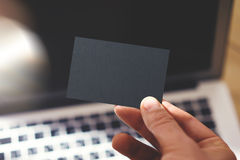 Closeup Photo Man Showing Blank Black Business Card and Using Modern Laptop Blurred Background. Mockup Ready for Private. Information. Sunlight Reflections Stock Image