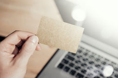 Closeup Photo Man Showing Blank Craft Business Card and Using  Modern Laptop Blurred Background. Mockup Ready for. Private Information. Sunlight Reflections Royalty Free Stock Photography