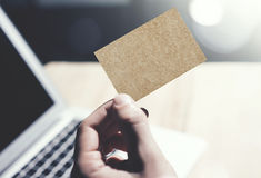 Closeup Photo Man Showing Blank Craft Business Card and Using  Modern Laptop.Wood table Blurred Background. Mockup Ready. For Private Information.Sunlight Royalty Free Stock Images