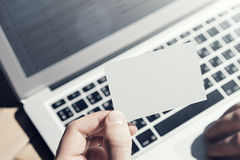 Closeup Photo Man Showing Blank White Business Card and Using  Modern Laptop on Wood table Blurred Background. Mockup. Ready for Private Information. Sunlight Stock Photos