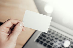 Closeup Photo Man Showing Blank White Business Card and Using  Modern Laptop.Wood table Blurred Background. Mockup Ready. Closeup Photo Man Showing Blank Craft Stock Photography