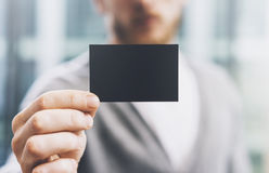 Closeup photo man wearing casual shirt and showing blank black business card. Blurred background. Ready for private. Man wearing casual shirt and showing blank Royalty Free Stock Image