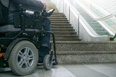 Closeup photo of man on a wheelchair in front of escalators and staircase with copy space stock photos
