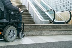 Closeup photo of man on a wheelchair in front of escalators and staircase with copy space stock photo