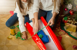 Closeup photo of mother and daughter making Christmas present an Royalty Free Stock Photos