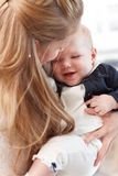 Closeup photo of mother hugging baby girl. Closeup photo of mother holding and hugging baby daughter Royalty Free Stock Images
