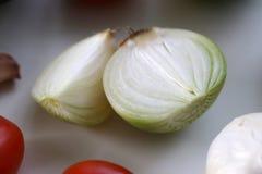 Onion Pieces on a White Table. A closeup photo of Onion Pieces. Photographed on a white table. Photo taken with a macro lens royalty free stock photos