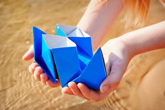 Closeup photo of paper ship in children hand Royalty Free Stock Photography