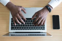 Closeup Photo of Person's Hands on Macbook Beside Space Gray Iphone 5s royalty free stock images