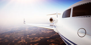 Closeup Photo Pilot Cabin White Luxury Generic Design Private Jet Airplane Flying Blue Sky sunset.Uninhabited Desert Royalty Free Stock Image
