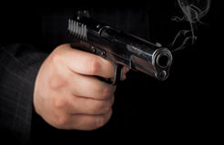 Closeup photo of pistol in hand with smoke Royalty Free Stock Photo