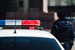 Closeup photo of police car with blue and red siren on the roof and defocused background. Closeup photo of police car with blue and red siren on the roof and royalty free stock image