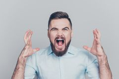 Closeup photo portrait of aggressive crazy mad bad furious man gesturing with hands isolated on grey background royalty free stock photography