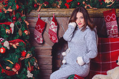 Closeup photo of pregnant woman posing against fireplace and Christmas tree Stock Photography