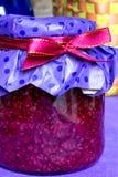 Closeup photo, raspberry jam-jar decorated  with ribbon, craft paper. Closeup photo of sweet raspberry jam-jar, with red  ribbon and craft paper, eco style Stock Photos