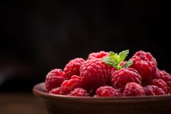 Red fresh raspberry. Closeup photo of red fresh raspberry on bowl, black background against Royalty Free Stock Images