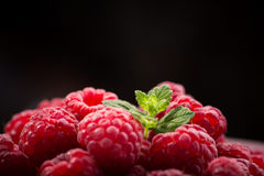 Red fresh raspberry. Closeup photo of red fresh raspberry on bowl, black background against Stock Image