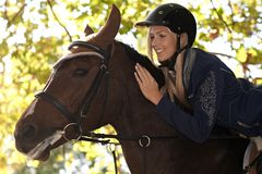 Closeup photo of rider and horse. Closeup photo of attractive female rider leaning over horse, smiling happy Stock Images