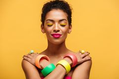 Closeup photo of satisfied naked mulatto woman with fashion make. Up and accessories posing on camera with crossed hands on shoulders over yellow Stock Photo