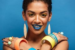 Closeup photo of sensual naked mulatto woman with fashion makeup. And accessories posing on camera with crossed hands on shoulders over blue Royalty Free Stock Photo
