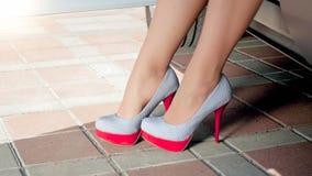 32bf22ef144 Closeup image of female legs in high heels at big car. Closeup photo of  female
